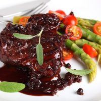Steak sauce with wine and onions, served with asparagus on a whi